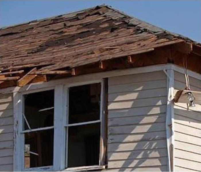 A damaged roof is shown with wind damage on the corner of a house